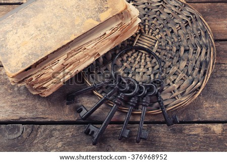 Composition of old books, keys and other things on wicker plate against wooden background, close up - stock photo