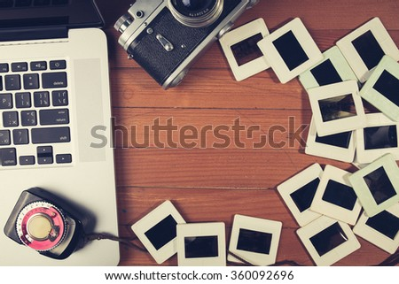 composition of old fashioned photo camera, laptop and photo slides on wooden table - stock photo