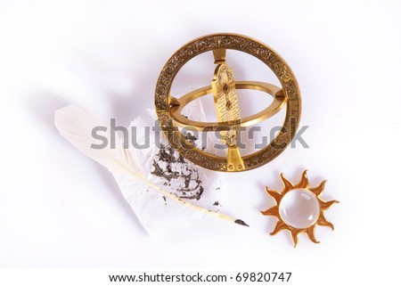 Composition of old measuring instrument for navigation, white feather and golden sun - stock photo