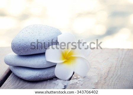 Composition of pebbles and fragipani flower on wooden background - stock photo
