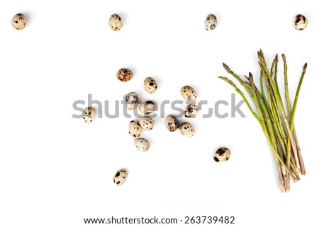 Composition of quail eggs and wild asparagus over white background, above view. - stock photo