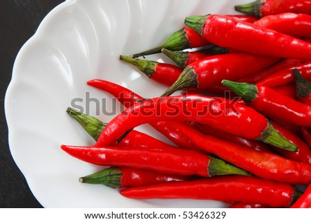 Composition of red chili pepper in white plate - stock photo
