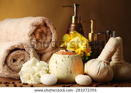 Composition of spa treatment on wooden table, on dark color background