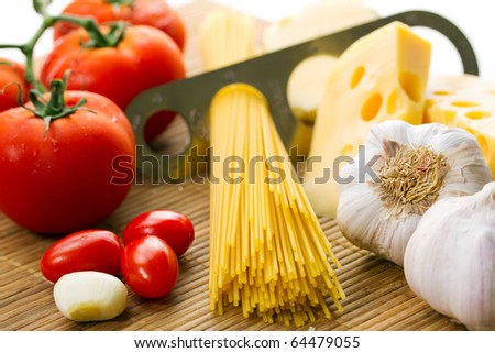 Composition of tomatoes, pasta, garlic and cheese - stock photo
