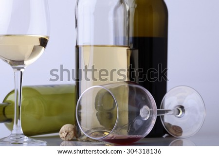 Composition of two glasses and bottles with white and red wine standing and lying with cork on table on white studio background, horizontal picture - stock photo
