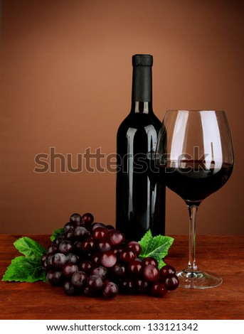 Composition of wine bottle, glass of red wine, grape on color background