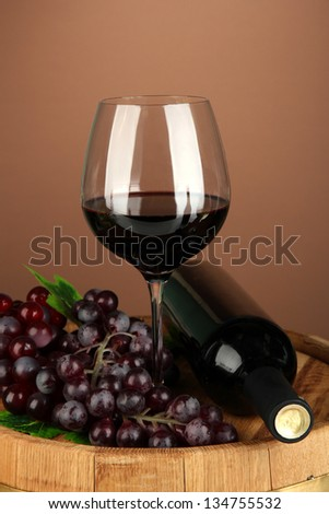 Composition of wine bottle, glass of red wine, grape on  wooden barrel, on color background - stock photo