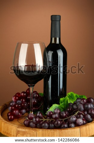 Composition of wine bottle, glass of red wine, grape on  wooden barrel, on color background