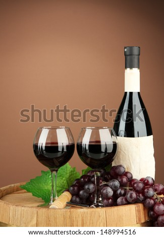 Composition of wine bottle, glasses and  grape,on wooden barrel, on brown background