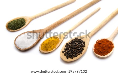 Composition of wooden spoons with dill powder, salt, curry, pepper and paprika, isolated on white