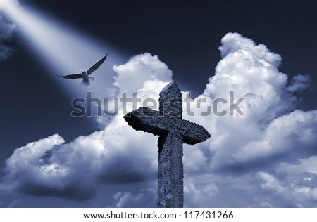 Composition with a stone cross against a beautiful cloudy sky. - stock photo