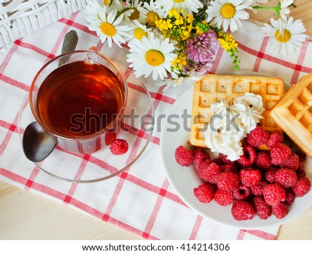 Composition with a tea cup, a raspberry and a bouquet of wild flowers