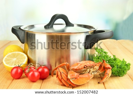 Composition with boiled crab, pan and vegetables on wooden table,on bright background
