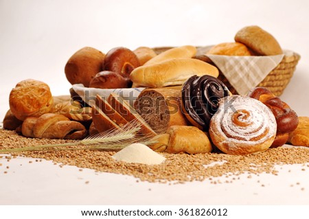 Composition with bread and rolls in wicker basket, combination of sweet pastries for bakery or market with wheat - stock photo