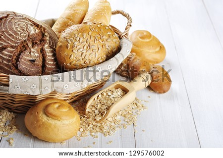 Composition with bread and rolls in wicker basket over white wooden background - stock photo