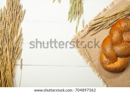 Composition with bread and rolls in wicker basket over white wooden background