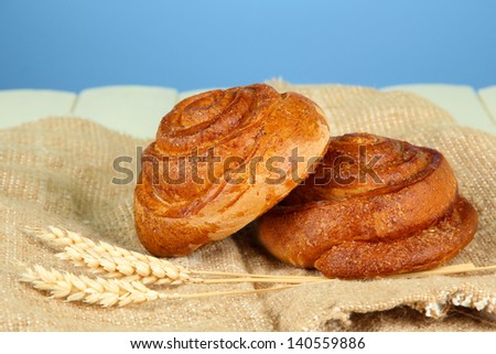 Composition with buns in wicker basket, on wooden table, on color background