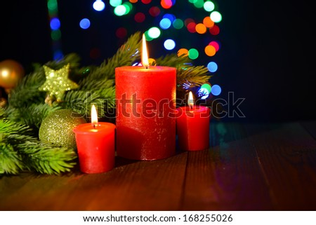 Composition with burning candles, fir tree and Christmas decorations on multicolor lights background - stock photo