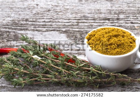 Composition with chili, thyme and white ceramic cup with spice on old wooden table. Selective focus. - stock photo
