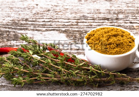 Composition with chili, thyme and white ceramic cup with spice on old wooden table. Selective focus. Toned. - stock photo