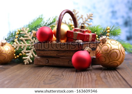 Composition with Christmas decorations in basket, fir tree on wooden table, on light background - stock photo