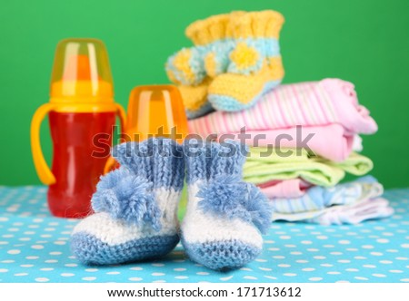Composition with crocheted booties for baby, clothes and other things on color background - stock photo