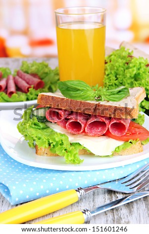 Composition with fruit juice and tasty sandwich with salami sausage and vegetables on color napkin, on wooden  table background