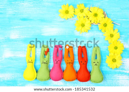 Composition with funny handmade Easter rabbits on wooden background