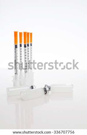 Composition with insulin bottles, insulin syringes and sugar