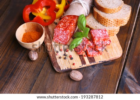 Composition with knife,  tasty salami sausage, sliced bread and pepper on cutting board, on wooden background - stock photo