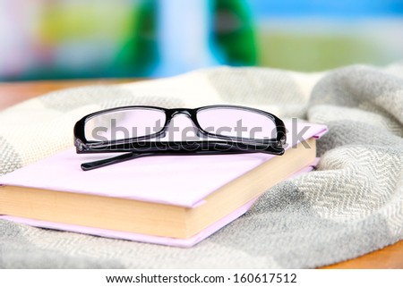 Composition with old book, eye glasses and plaid on bright background