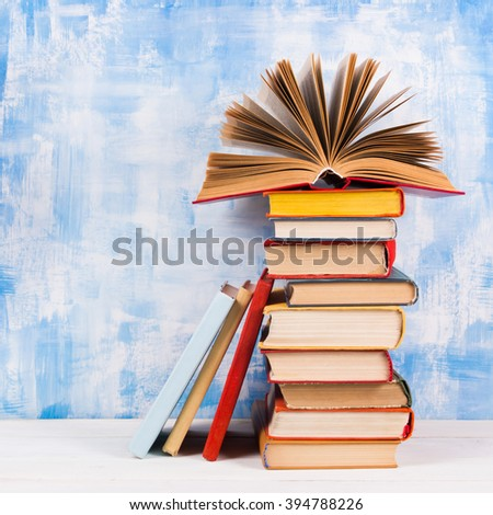 Composition with old vintage colorful hardback books, diary on wooden deck table and artistic blue background. Books stacking. Back to school. Copy Space. Education background - stock photo