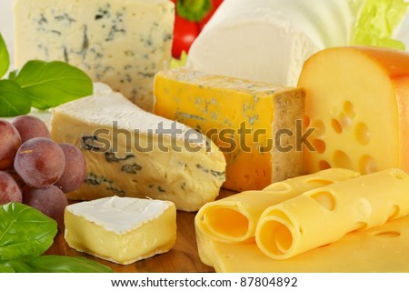 Composition with pieces of cheese on breadboard