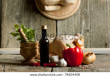 Composition with raw chicken, onion, garlic, red paprika and vintage mortar on old wooden table with mirror reflex