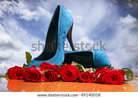 Composition with red roses and blue female shoes on sky background - stock photo