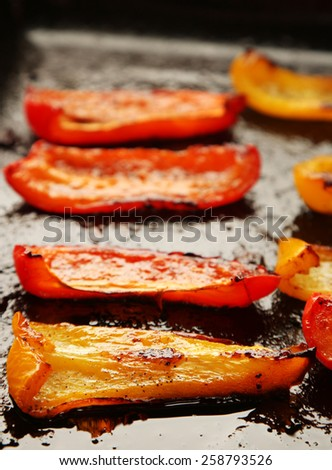 Composition with roasted sliced pepper on pan, close-up - stock photo