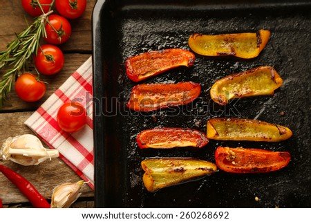 Composition with roasted sliced pepper on pan, tomatoes and rosemary sprigs on wooden background - stock photo