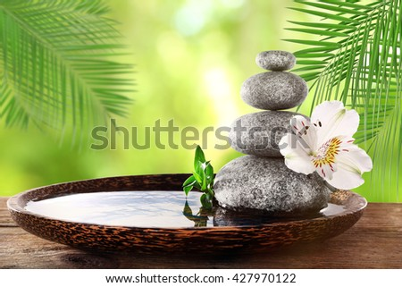 Composition with spa stones and flower on natural blurred background - stock photo