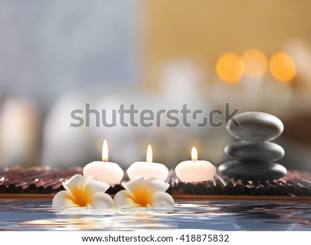 Composition with spa stones, flowers and candles in water on blurred background - stock photo