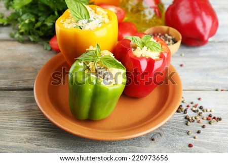 Composition with stuffed peppers on plate and fresh herbs, spices and vegetables, on wooden background - stock photo