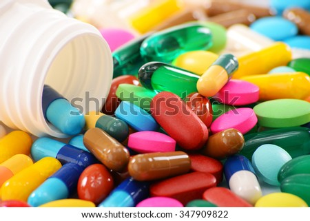 Composition with variety of drug pills and container. - stock photo