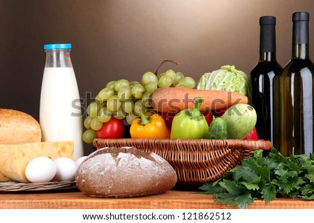 Composition with vegetables  in wicker basket on brown background - stock photo