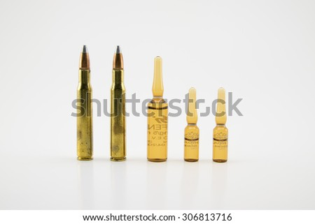 Composition with vials and bullets on white background. - stock photo