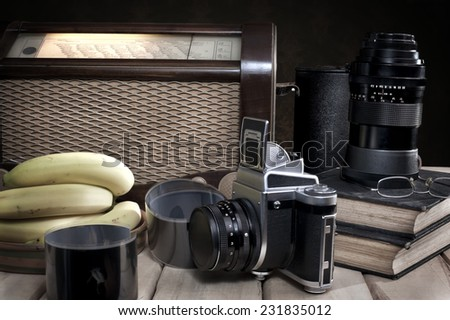 Composition with vintage items on table Vintage radio, books, glasses, old camera, whiskey and bananas on wooden surface - stock photo