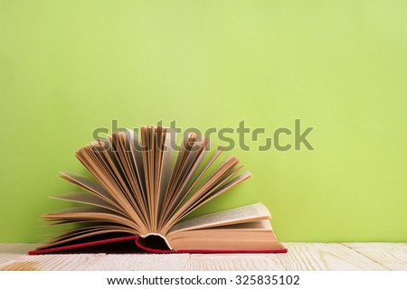 Composition with vintage old hardback books, diary, fanned pages on wooden deck table and green background. Books stacking. Back to school. Copy Space. Education background - stock photo