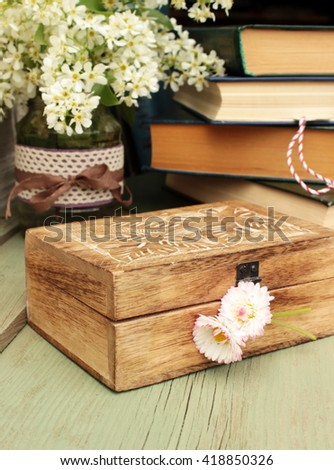 Composition with vintage wooden box decorated with small bunch of flowers, stack of books and little case decorated with lace and ribbon. Rustic decor elements - stock photo