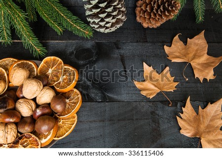 Compositionon wood background for branches and a decorative dry oranges, pain fruit and leafs for informal dinners or family celebrations in autumn winter season