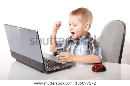 Computer addiction emotional child boy with laptop notebook playing games isolated on white background