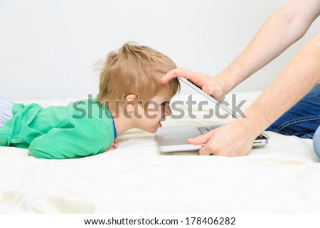computer addiction - father taking computer from the child - stock photo