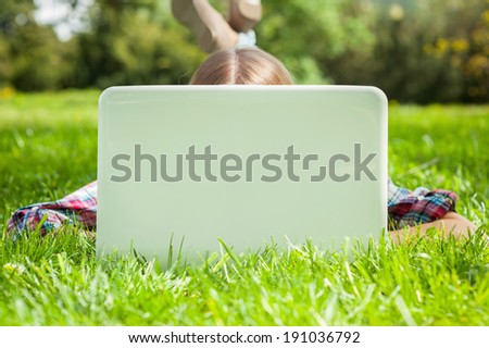 Computer and fresh air. Woman hiding face behind laptop monitor while lying on the grass in park - stock photo